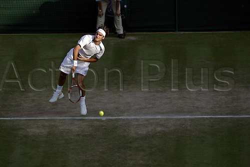27 June 2005: Swiss player Roger Federer (SUI) serving during his fourth round singles match against Ferrero at the All England Lawn Tennis Championships, Wimbledon, London. Federer won the match 6-3, 6-4, 7-6. Photo: Glyn Kirk/Actionplus..050627 mens man male serve service