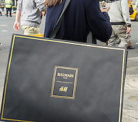 Shoppers outside an H&M store in New York with their Balmain x H&M purchases on Thursday, November 5, 2015. The collection, designed by the young head of Balmain, Olivier Rousteing, was highly anticipated by fashionistas and drew crowds around the world. In New York H&M instituted a wristband system to time when shoppers could arrive to control crowds. (© Richard B. Levine)