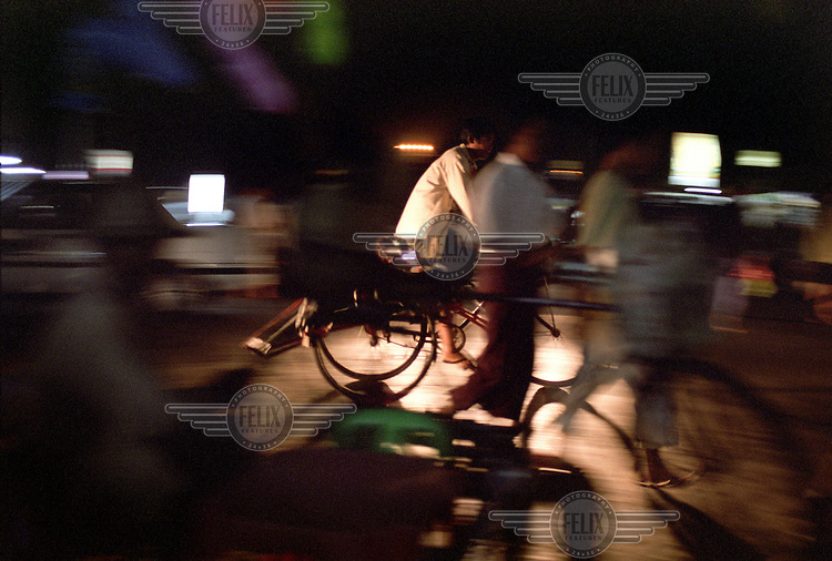 People cycle and walk along an urban street in Rangoon (Yangon) at night time. ..