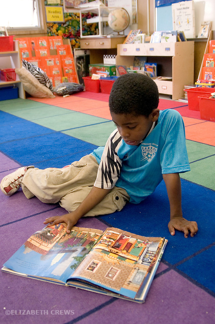 "Oakland CA 1st grade student looking at book on reading mat (part of classroom organization through ""Open Court"" educational program"