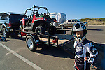 Young rider at staging area with sand machines, trucks and trailers in the background