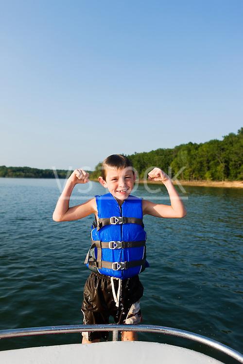 USA, Missouri, Stockton, Stockton Lake, boy (6-7) wearing lifejacket flexing muscles