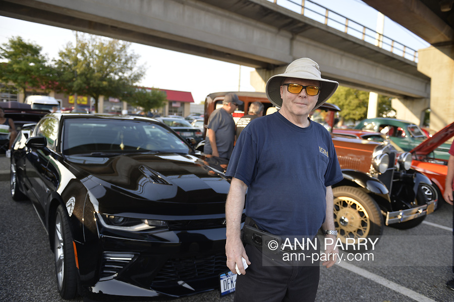 """Bellmore, New York, USA. August 24, 2018. """"Mr. Blowtorch"""" stands next to his black Chevrolet SS at Bellmore Friday Night Car Show, in parking lot of LIRR Bellmore station."""
