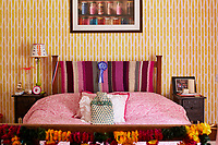 Bold colour and patterns feature in the guest bedroom with yellow wallpaper and shades of pink used in the bedcover and a crochet blanket.