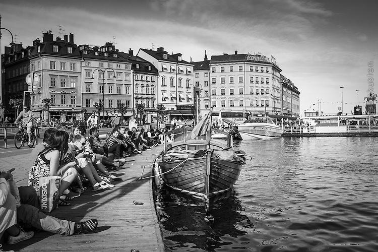 Träbåt och människor i sol vid Munkbron Gamla stan i Stockholm