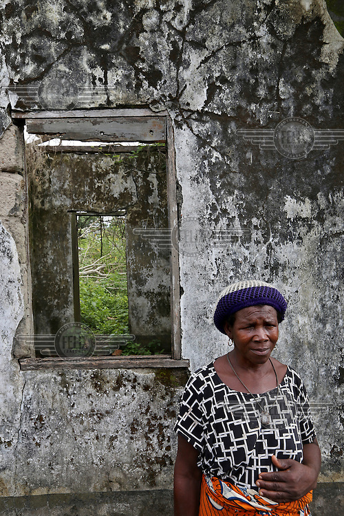 A woman stands in front of her derelict house in the Oduoha community.<br /> The Rumuekpe community suffered much damage during the conflict among various rival militants and cult gangs over access to oil money. The inter-communal violence killed many people, including women and children, between 2005-08. Thousands more were displaced by fighting that left homes, schools and churches in ruins with many suffering poverty and homelessness.