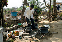 A local resident fills up the reserve water storage in the courtyard of his house in Ambedkar Nagar in Medak, Telangana, India.