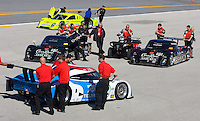 Crew members push their cars around during a group photo shot as teams arrive at Daytona International Speedway for the Rolex 24 at Daytona, Daytona Beach, FL January 27, 2010.  (Photo by Brian Cleary/www.bcpix.com)