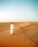 SAUDI ARABIA, Najran, teenage boy standing on sand dune in The Empty Quarter