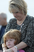 Arlington, VA - September 11, 2008 -- Stephanie Dunn Simone and her daughter, Alice Dunn, bow thier heads during the the Pentagon Memorial dedication ceremony Sept. 11, 2008. The national memorial is the first to be dedicated to those killed at the Pentagon on Sept. 11, 2001. The site contains 184 inscribed memorial units honoring the 59 people aboard American Airlines Flight 77 and the 125 in the building who lost their lives that day. Dunn Simone's husband, Navy Commander Pat Dunn, was killed during the attack. .Credit: Chad McNeeley - DoD via CNP