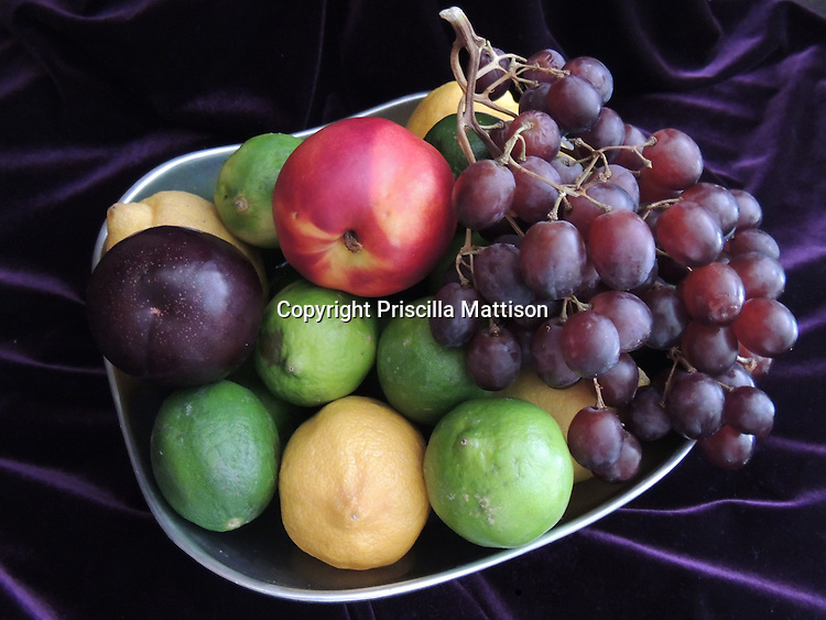 A contemporary still life features fruit in a silver colored bowl against a purple backdrop.