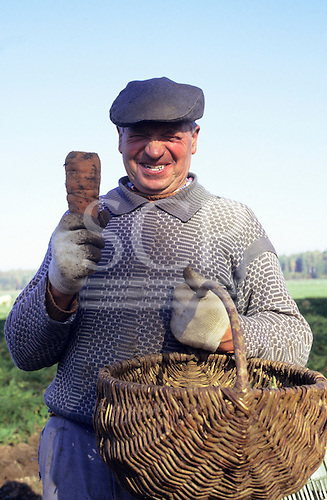 Poland. Smiling man holding a large carrot and a basket.