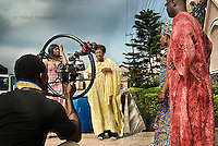 Director Ola Orlando Shoyinka (far left) uses a digital camera to film a scene involving actors Ufuoma Ejenobor, Patience Ozokwo, Ngozi Doomanbey and Richard Dike (left to right) on the set of a Nollywood movie production. Almost all movies in Nollywood are shot digitally.