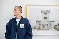 Mitchell with his pintop patch and the original artwork. Free Architecture at the Chalton Gallery, London, England, Great Britain
