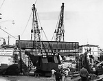 Suspended in mid-air and supported only by two huge cranes, this railroad trestle is slowly being settled into place at the South Leonard Street - Washington Avenue overpass as part of the New Haven Railroad's rehabilitation program. the section was damaged in the August 19th flood. 13 October 1955.