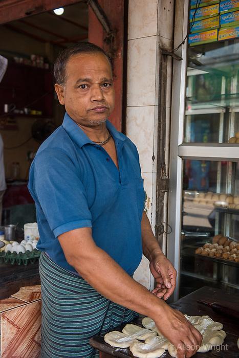 Bangladesh, Jhenaidah. Man making chapatis in the market.