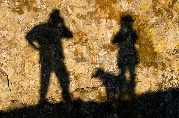 Shadow of Man, Woman and Dog on a Rock