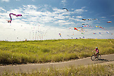 USA, Washington State, Long Beach Peninsula, International Kite Festival, woman riding her bike on the path that runs parallel to the Long Beach Boardwalk