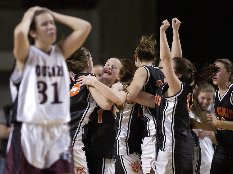 Quaboag's Amy Vayda walks off the court as Lee celebrates its 54-53 overtime win at the conclusion of a high school state semifinal basketball game in Amherst, Massachusetts.