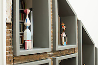 A Victorian home has been given a modernist aesthetic. For storage and display, a shelf lighted with LED bulbs begins at the front door and runs like ribbon throughout the house, providing visual continuity between its rooms. A collection of wooden suffragette dolls is displayed on the shelving.