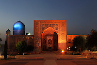 View from the front of the Tillyah-Kori Madrasah, 1646-60, Registan, Samarkand, Uzbekistan, pictured on July 16, 2010, dramatically floodlit at night. The Tillyah-Kori (gilded) Madrasah is part of the Registan Ensemble, surrounding a magnificent square. Commissioned by Yalangtush Bakhadur it is not only a school but also the grand mosque whose lavishly gilded main hall in Kundal style justifies the name. The 75 metre main facade is two-storied with corner turrets and  decorated in brilliant mosaic. Around the courtyard are the dormitory cells.  The dome was only completed during the 20th century Soviet restoration. Samarkand, a city on the Silk Road, founded as Afrosiab in the 7th century BC, is a meeting point for the world's cultures. Its most important development was in the Timurid period, 14th to 15th centuries. Picture by Manuel Cohen.
