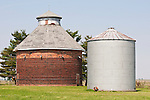 Masonry round corn crib (barn) at a farm, metal grain storage tanks, rural Ill.