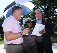 STAFF PHOTO ANDY SHUPE - The Rev. Steve Dixon, pastor of Christian Life Cathedral, right, sings alongside Sheriff Tim Helder, left, and Betty Davis during a dedication ceremony Sunday, Sept. 21, 2014, for the Gehring Cemetery at Christian Life Cathedral in Fayetteville.
