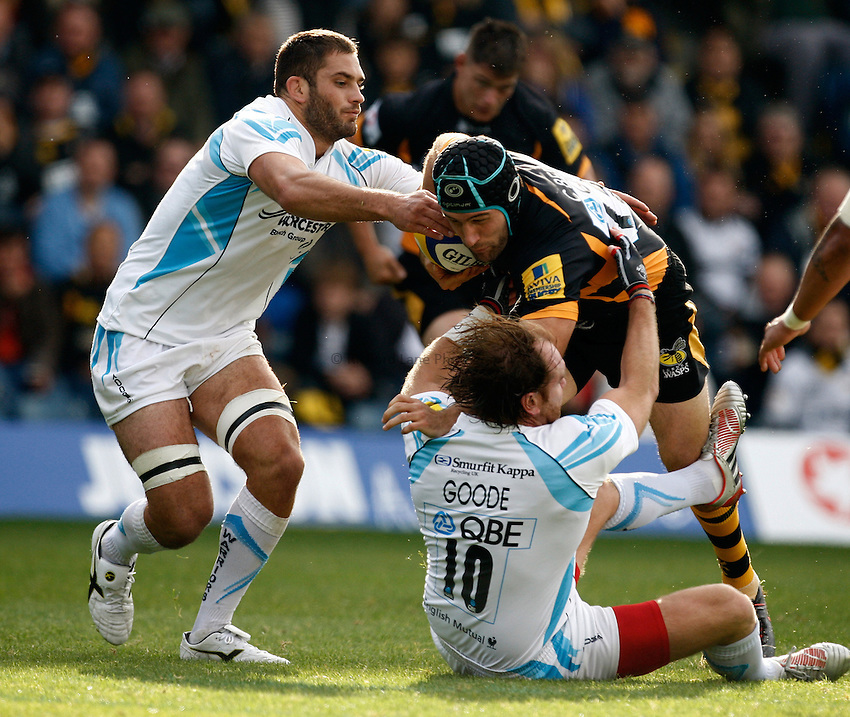 Photo: Richard Lane/Richard Lane Photography. London Wasps v Worcester Warriors. 07/09/2012. Wasps' Chris Bell is tackled by Warriors' Andy Goode and Sam Betty.