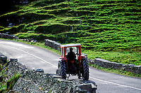 Farmer driving a tractor on a narrow country road, Ireland
