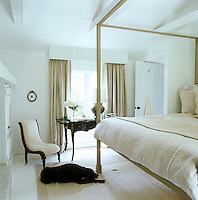 One of the dogs asleep on a rug in the master bedroom with its calming colour scheme of white and beige