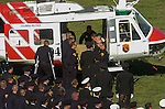September 20, 2004 Angels Camp, California --Tuolumne Fire –- Firefighter Jon Andahl, injured in the Tuolumne Fire that killed fellow crew member Eva Marie Schicke, walks with crutches to CDF helicopter 404 at the end of Schicke's memorial service as Schicke's casket is carried to the helicopter by her Helitack crew members for her last flight home. The memorial service was held at the Calaveras County Fairgrounds.  The Tuolumne Fire was a small very fast-moving fire that started around noon on September 12, 2004 near Lumsden Bridge at the bottom of the Tuolumne River.  The fire moved rapidly up the 80-plus-degree slope catching Cal Fire Helitack firefighters, tragically killing firefighter Eva Marie Schicke and injuring five others.