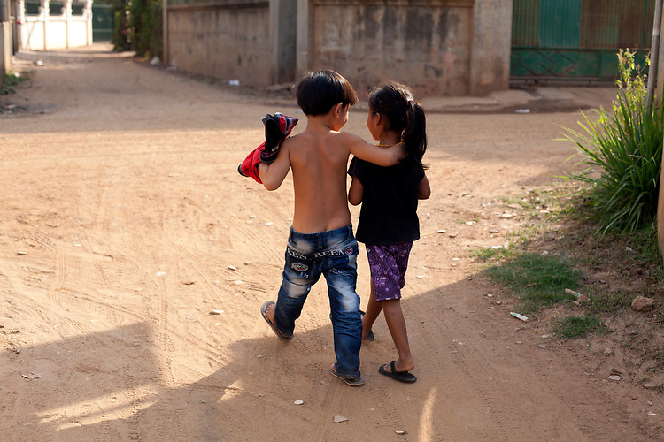 A young boy and girl walk arm and arm in a small village outside of Phnom Penh, Cambodia. <br /> <br /> Photos &copy; Dennis Drenner 2013.