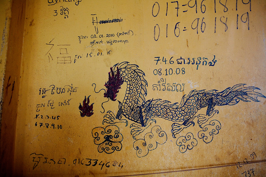 Drawings, phone numbers and dates on a wall of one of the classroom and dorm room combo at Orkas Khnom, or My Chance, a government-run facility where youth and young men are brought here by their families or by arrest from police to be re-educated from drug addiction, just outside Phnom Penh, Cambodia, on Tuesday, May 11, 2010.