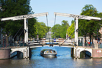 Pleasure boat taking tourist on sightseeing cruise tour of famous canals and bridges of  Amsterdam, Holland