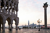 ITALY, Venice.  A view of Doge's Palace on the left and the Column of the Lion on the right at the Piazza San Marco. The island of San Giorgio Maggiore can be seen in the distance, dominated by the tower and dome of the Church of San Giorgio Maggiore.