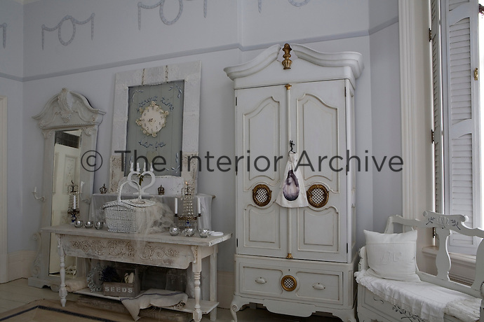 A console table decorated with candelabra is flanked by a large mirror and a Swedish cupboard