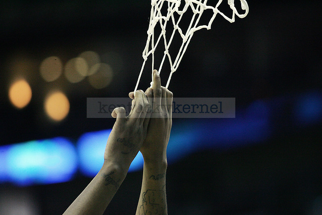 Darnell Dodson hangs on to the net during an open practice before UK's first round of the NCAA tournament at New Orleans Arena on Wednesday, March 17, 2010. Photo by Adam Wolffbrandt | Staff