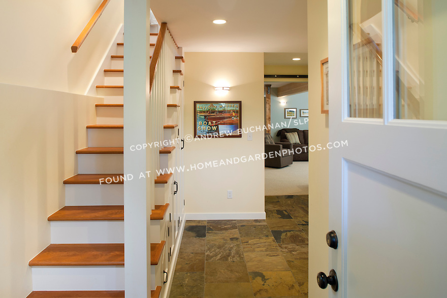 An open staircase leads into the mudroom of this light-filled, newly-remodeled basement.  This image is available through an alternate architectural stock image agency, Collinstock located here: http://www.collinstock.com
