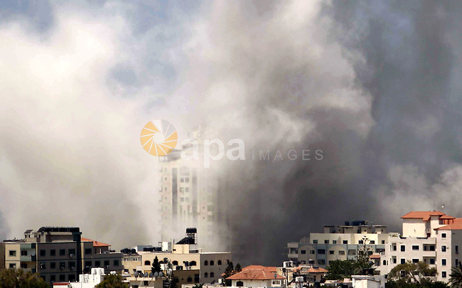 Smoke rises following an Israeli air strike in the east of Gaza city on August 09, 2014. Israeli warplanes carried out 30 air strikes over Gaza on August 9, 2014, killing five Palestinians, as militants fired six rockets into Israel, leaving international mediators scrambling to rescue ceasefire talks. Photo by Ashraf Amra
