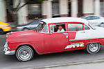 Havana, Cuba; a classic red and white 1955 Chevy Bel Air driving along the Paseo de Marti past the Saratoga Hotel