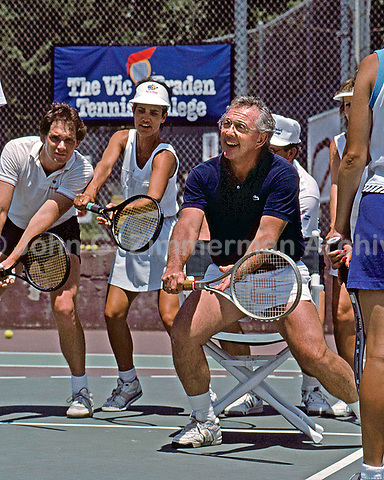 Vic Braden demonstrates how to bend knees on a backhand by sitting in a chair, Vic Braden Tennis College, Coto de Caza, Ca, 1984. Photo by John G. Zimmerman