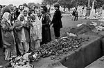 Blair Peach funeral. Southall west London 1979. Members of the Sheik community  leave red carnations at his graveside.