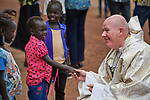 Father Tony O'Riordan, SJ, greets children after Catholic Mass in Bunj, the host community for the Doro Refugee Camp in Maban County, South Sudan. Doro is one of four camps in Maban that together shelter more than 130,000 refugees from the Blue Nile region of Sudan. Jesuit Refugee Service provides educational and psycho-social services to both refugees and the host community. Fr. O'Riordan directs the JRS work in Maban.<br /> <br /> Misean Cara supports the work of JRS in the Maban camps and host community.