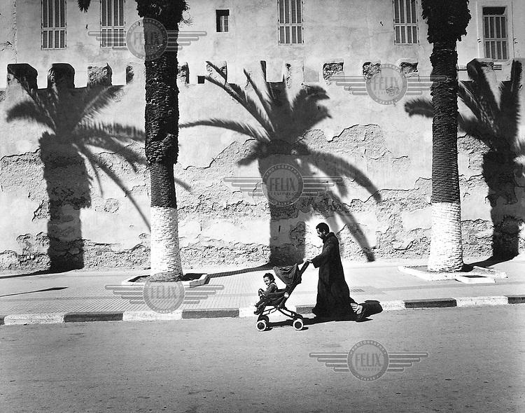Morocco, Essaouira, November 2002..Father walking with his child in a pram along the citywalls of Essaouira..Harbourtown with fishingport. In the 15th century established as Portugese commercial and military bridgehead, named Mogador..Photo: Tim Dirven/Panos Pictures..Marokko. Essauoira, november 2002..Vader wandelt met zijn kind in een kinderwagen langs de stadswal rond de stad Essaouira..Essaouira is een havenstadje met vissershaven. .In de 15de eeuw gesticht door Portugezen als commercieel en militair bruggehoofd, Mogador genaamd..foto: Tim Dirven/HH