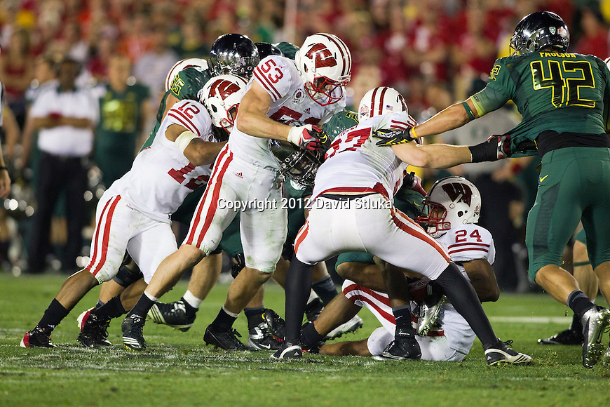 Wisconsin Badgers defense gang tackles an Oregon Ducks ball carrier during the 2012 Rose Bowl NCAA football game in Pasadena, California on January 2, 2012. The Ducks won 45-38. (Photo by David Stluka)
