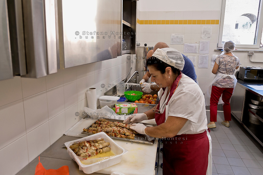 """ROME, ITALY - SEPTEMBER 24: The cook prepares dinner in the kitchen at the hostel  """"Don Luigi Di Liegro"""" of the Caritas of Rome in Via Marsala, Rome. The new facility of 500 for the evening canteen and 300 beds to the hostel,  hosts marginalized people. The hostel opened in 1987 has been renovated to make it more efficient, the social reintegration of the guests  on September 24, 2016 in Rome, Italy."""
