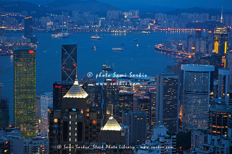 Kowloon skyline and Victoria Harbour at dusk, Hong Kong Island, Hong Kong, China.