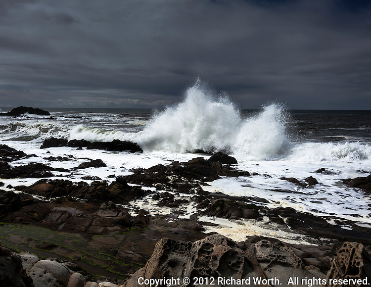 Under an ominous gray sky, waves crash with plumes of white at Bean Hollow State Beach on the California coast.