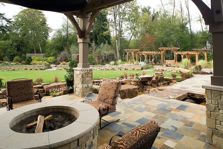 An outdoor firepit on a covered stone patio provides year-round enjoyment in this Pacific Northwest home. This image is available through an alternate architectural stock image agency, Collinstock located here: http://www.collinstock.com