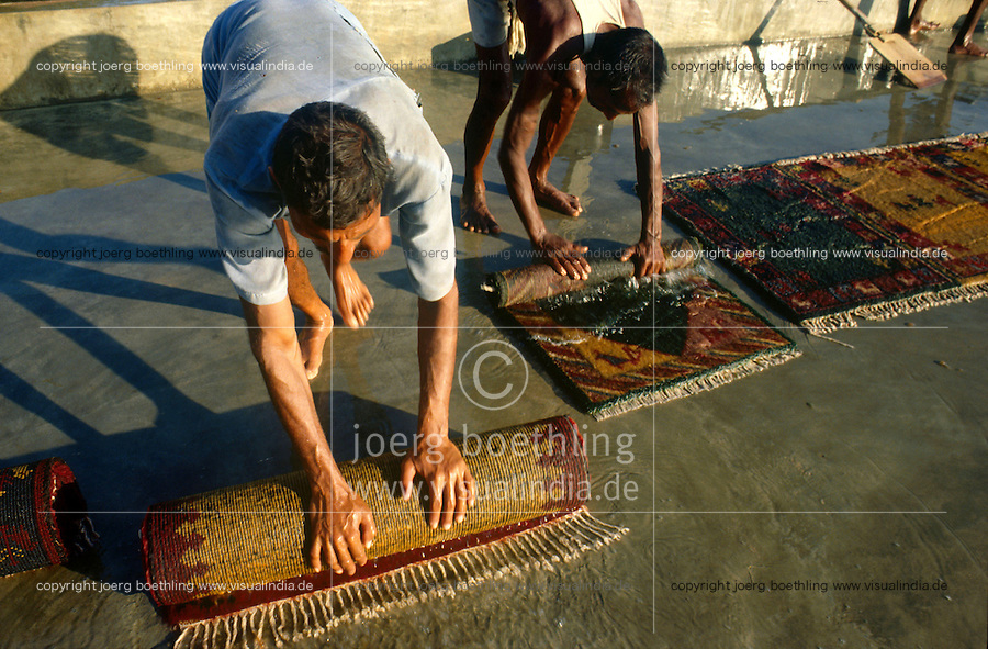 INDIA Uttar Pradesh, Badohi, worker wash carpets at carpet manufacture in a village in the carpetbelt between Badohi and Mirzapur / INDIEN, Arbeiter waschen Teppiche in einer kleinen Manufaktur in einem Dorf